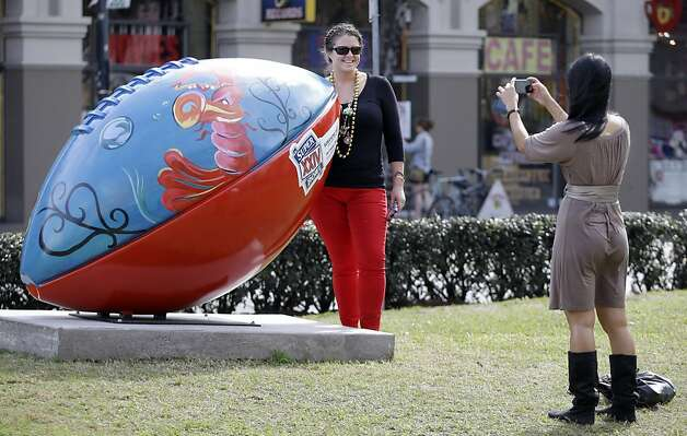 Kendall Williamson, left, of St. Louis, stands by a giant football and has her picture made by Heather Chau, right, on Sunday, Jan. 27, 2013, in New Orleans. The San Francisco 49ers and the Baltimore Ravens are scheduled to play in the NFL Super Bowl XLVII football game on Feb. 3. (AP Photo/Mark Humphrey) Photo: Mark Humphrey, Associated Press