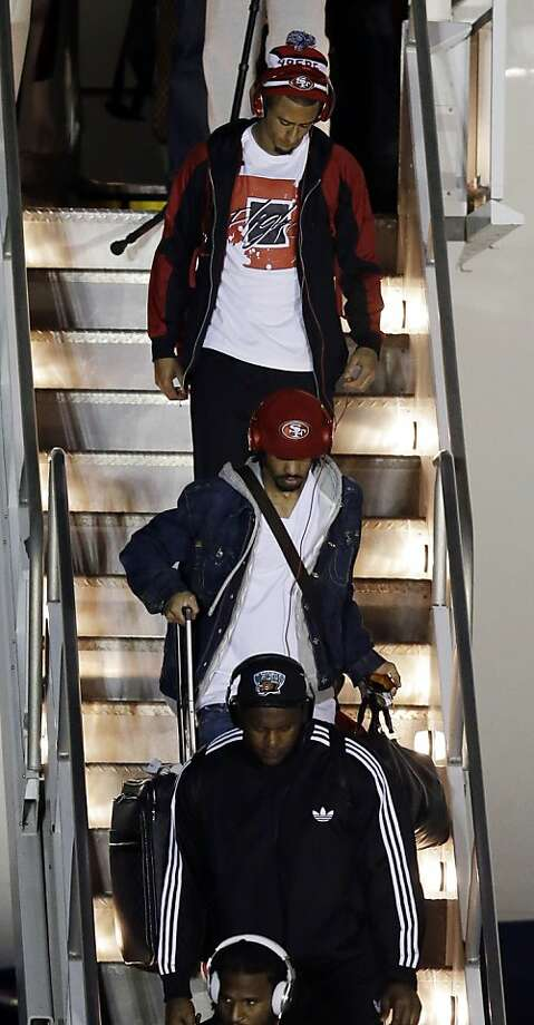San Francisco 49ers quarterback Colin Kaepernick (7) arrives with teammates at the Louis Armstrong International Airport for the NFL Super Bowl XLVII football game Sunday, Jan. 27, 2013, in New Orleans. (AP Photo/David J. Phillip) Photo: David J. Phillip, Associated Press