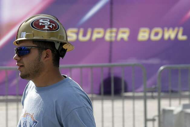 A worker in a San Francisco 49ers hard hat walks outside of the Mercedes-Benz Superdome as preparations take place for the NFL Super Bowl XLVII football game on Sunday, Jan. 27, 2013, in New Orleans. The Baltimore Ravens and San Francisco 49ers are scheduled to play in Super Bowl XLVII on Sunday, Feb. 3. (AP Photo/Patrick Semansky) Photo: Patrick Semansky, Associated Press