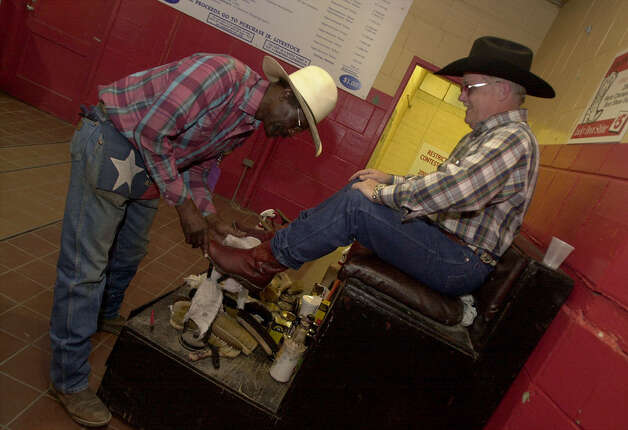 "Alvin Sheppard (left) shines Chip Hawkins' boots at the San Antonio Stock Show & Rodeo on Feb. 7, 2001. Sheppard has been proclaimed ""PRCA World Champion Rodeo Boot Shine Expert"" and has been shining boots for nearly 30 years. Photo: Kin Man Hui, San Antonio Express-News"