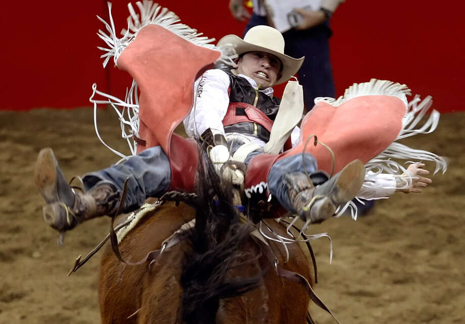 Matt Bright of Azle hangs on in the opening round of the bareback riding competition at the San Antonio Stock Show & Rodeo on Feb. 5, 2010. Photo: Kin Man Hui, San Antonio Express-News