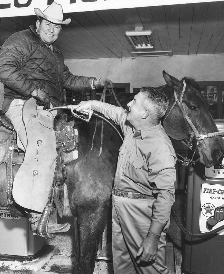 "An attendant gives a cowboy a ""fill up"" at the San Antonio Stock Show & Rodeo on Feb. 8, 1971. Photo: San Antonio Express-News File Photo"