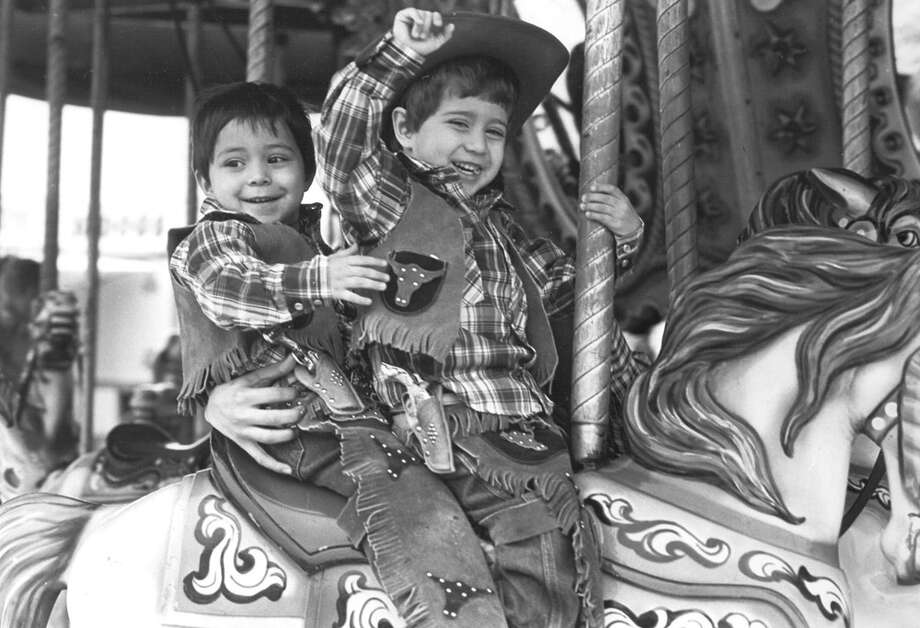 Twins Larry and Leroy Narvaez tame a horse on the merry-go-round at the San Antonio Stock Show & Rodeo on Feb. 8, 1985. Photo: San Antonio Express-News File Photo
