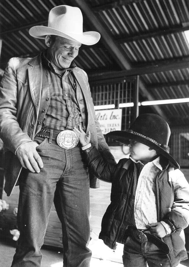 Bob Wegner, 50, shows off his world champion bull rider belt buckle to Christopher Todd, 4, at the San Antonio Stock Show & Rodeo on Feb. 11, 1985. Wegner was a champion from 1963-64. Photo: San Antonio Express-News File Photo