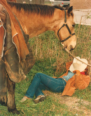 Laura Galbraith, 19, of Sinton takes a short nap while her horse Dunny watches over her as the South Texas trail riders stop for lunch and rest in Karnes City on Feb. 9, 1988. They are on their way to the San Antonio Stock Show & Rodeo. Photo: San Antonio Express-News File Photo
