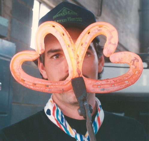 David Mayfield of Pipe Creek holds two heart-shaped horseshoes which he is selling for $3 for Valentines at the San Antonio Stock Show & Rodeo on Feb. 13, 1989. Photo: San Antonio Express-News File Photo