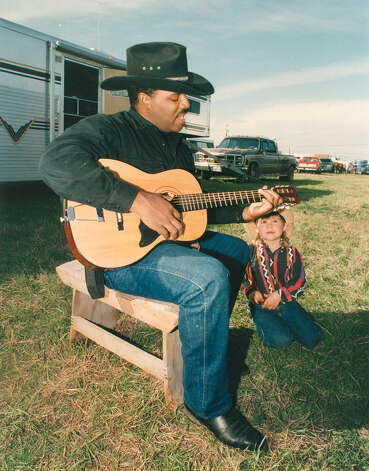 South Texas trail rider Chris Sizer strums a tune as Andy Bjorgaard, 5, listens at the San Antonio Stock Show & Rodeo campgrounds on Feb. 7, 1993. Photo: San Antonio Express-News File Photo