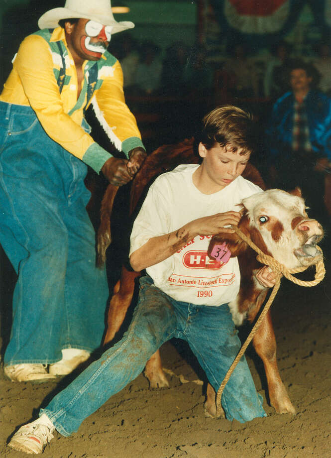 A boy participates in the calf scramble with the help of a barrelman at the San Antonio Stock Show & Rodeo on Feb. 10, 1990. Photo: San Antonio Express-News File Photo
