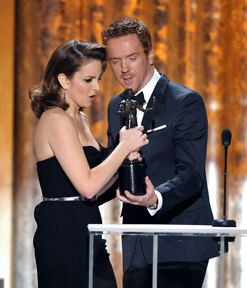 "Damian Lewis, right, presents the award for outstanding female actor in a comedy series to Tina Fey for ""30 Rock""at the 19th Annual Screen Actors Guild Awards at the Shrine Auditorium in Los Angeles on Sunday Jan. 27, 2013. (Photo by John Shearer/Invision/AP) Photo: John Shearer, Associated Press"