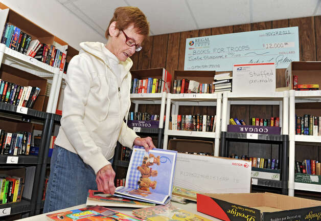Ellen Keegan, of Books for Troops, goes through donated children's books at Old Halfmoon Town Hall on Friday Jan. 25, 2013 in Halfmoon, N.Y. The organiziation Books for Troops is boxing up children's books to send to troops in Afghanistan. The soldiers requested children's books so they can read bedtime stories to their children at night over Skype. (Lori Van Buren / Times Union) Photo: Lori Van Buren