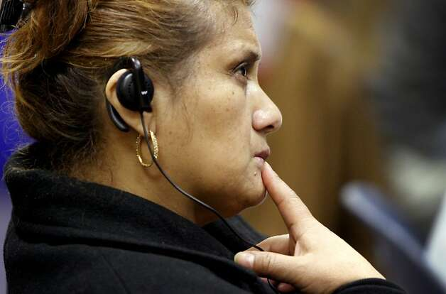 Nativadad Lopez uses an earpiece to listen to a live translator during the talk. Photo: Sarah Rice, Special To The Chronicle