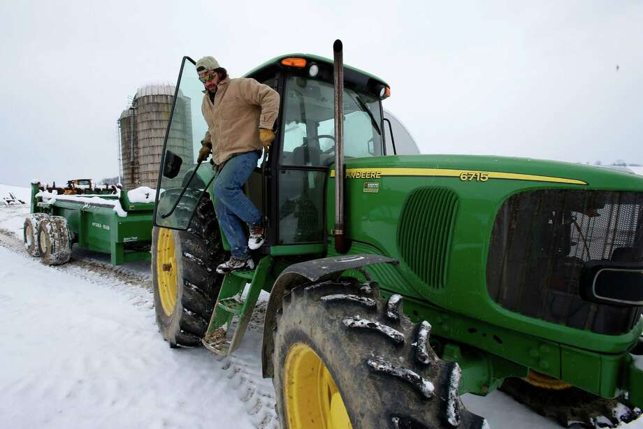 In this Saturday, Jan. 26, 2013 photo, Shawn Georgetti climbs out of his John Deere tractor on his 167-acre family dairy farm in Avella, Pa. With royalties from a Range Resources gas well on his property, Georgetti has been able to buy newer farm equipment that's bigger, faster, and more fuel-efficient. (AP Photo/Gene J. Puskar) Photo: Gene J. Puskar