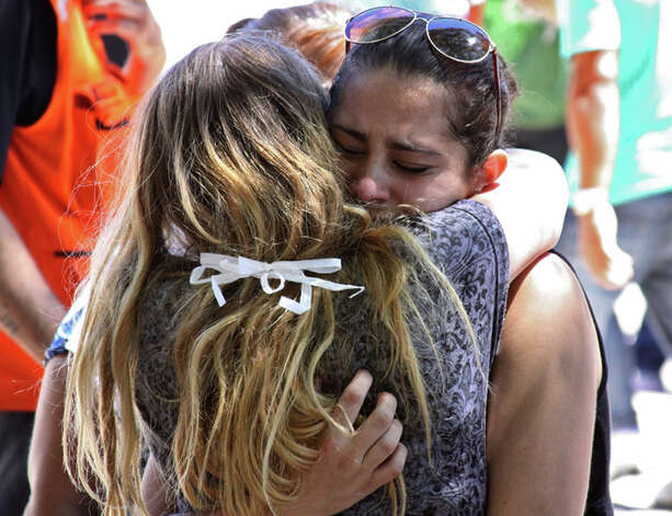 Relatives of victims react in Santa Maria city, Rio Grande do Sul state, Brazil, Sunday, Jan. 27, 2013. A blaze raced through the crowded nightclub in southern Brazil early Sunday, killing more than 200 people as the air filled with deadly smoke and panicked party-goers stampeded toward the exits, police and witnesses said. It appeared to be the world's deadliest nightclub fire in more than a decade.(AP Photo/Evandro Sturm) Photo: Evandro Sturm