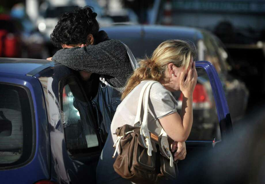 Relatives of victims react as they wait for news near the Kiss nightclub in Santa Maria city,  Rio Grande do Sul state, Brazil, Sunday, Jan. 27, 2013.  According to police more than 200 died in the devastating nightclub fire in southern Brazil.  Officials say the fire broke out at the club while a band was performing. (AP Photo/Ronald Mendes-Agencia RBS) Photo: Ronald Mendes