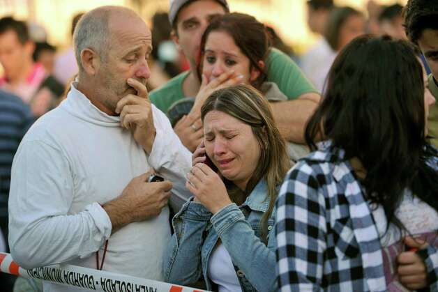 Relatives of victims react as they wait for news in fron of the Kiss nightclub in Santa Maria city,  Rio Grande do Sul state, Brazil, Sunday, Jan. 27, 2013.  According to police more than 200 died in the devastating nightclub fire in southern Brazil.  Officials say the fire broke out at the club while a band was performing. (AP Photo/Ronald Mendes-Agencia RBS) Photo: Ronald Mendes