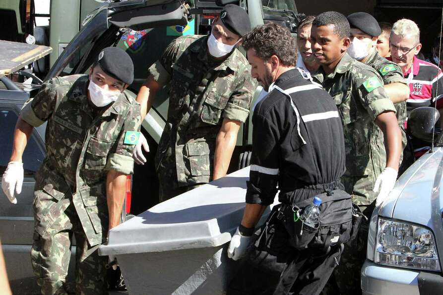 Brazil's soldiers carry a container with the remains of a victim outside a gymnasium where bodies we