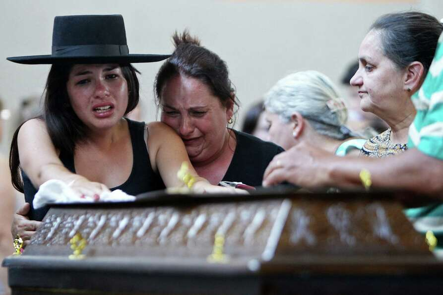 Relatives cry next to a coffin at a gymnasium where bodies were brought for identification in Santa