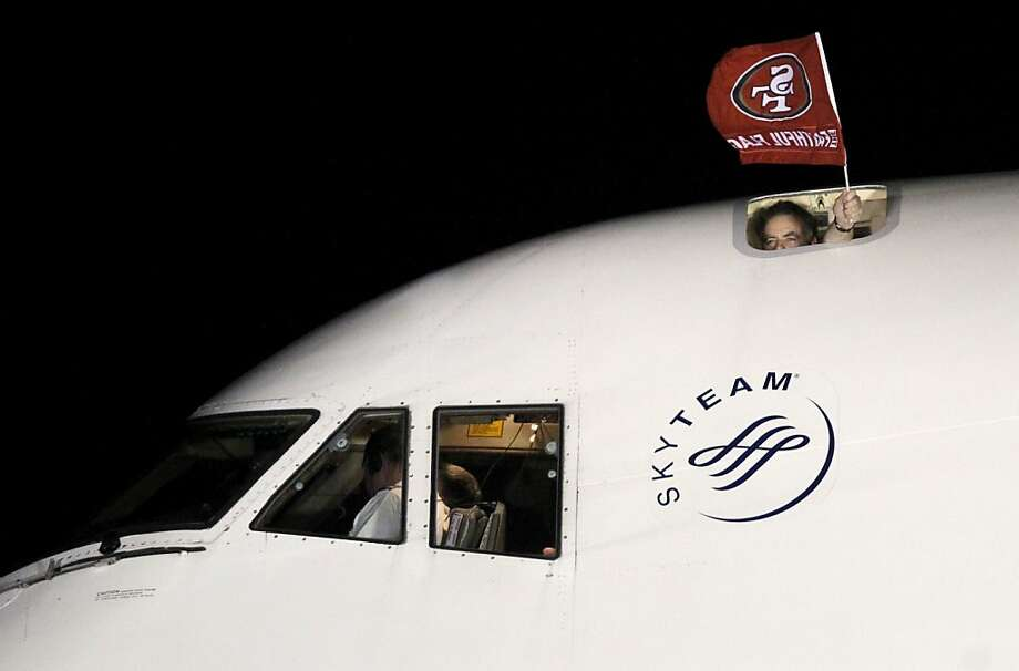 Someone onboard holds a 49er flag out of the top of the plane as the San
