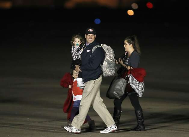 Niners head coach Jim Harbaugh arrives in New Orleans with daughters Addison (bottom left) and Katherine (in his arms). The woman behind them was not identified. Photo: Michael Macor, The Chronicle
