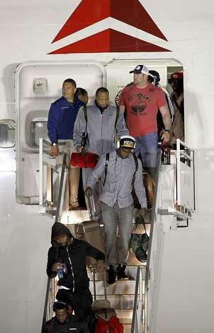 The 49ers' players descend the steps of their plane and enter the maelstrom of Super Bowl week in New Orleans. Photo: Michael Macor, The Chronicle