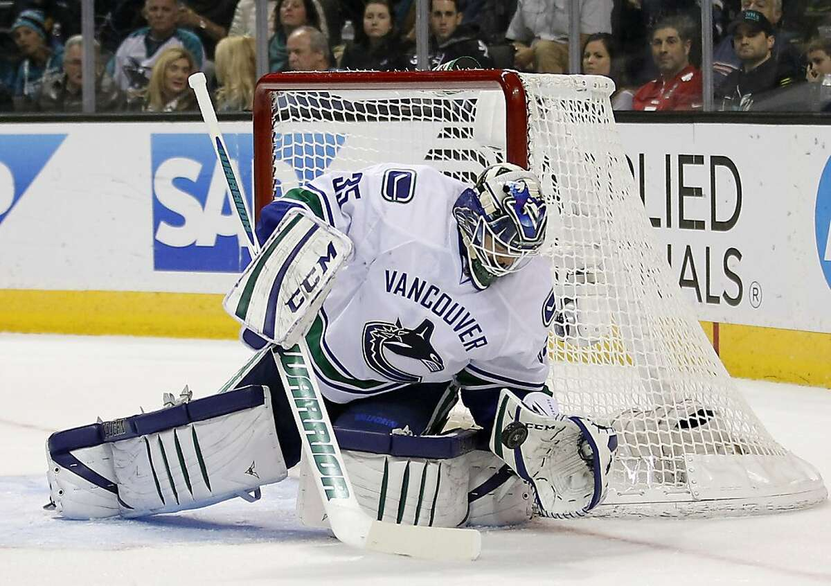 Vancouver Canucks goalie Cory Schneider makes a glove save against the San Jose Sharks during the first period of an NHL hockey game in San Jose, Calif., Sunday, Jan. 27, 2013. (AP Photo/Tony Avelar)