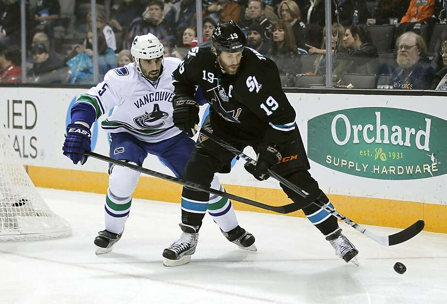 San Jose Sharks center Joe Thornton (19) works for the puck against Vancouver Canucks defenseman Jason Garrison (5) during the first period of an NHL hockey game in San Jose, Calif., Sunday, Jan. 27, 2013. (AP Photo/Tony Avelar) Photo: Tony Avelar, Associated Press
