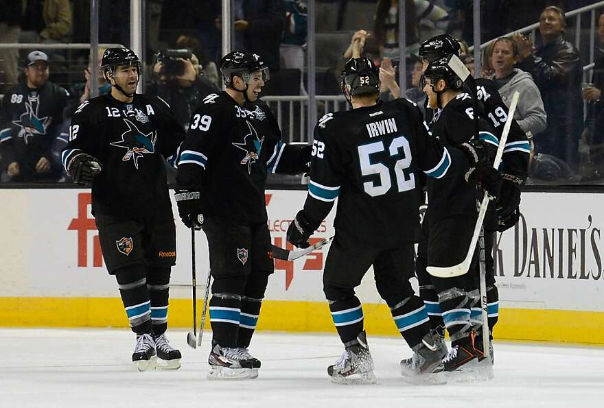 SAN JOSE, CA - JANUARY 27:  Joe Pavelski #8 of the San Jose Sharks is congratulated by teammates Joe