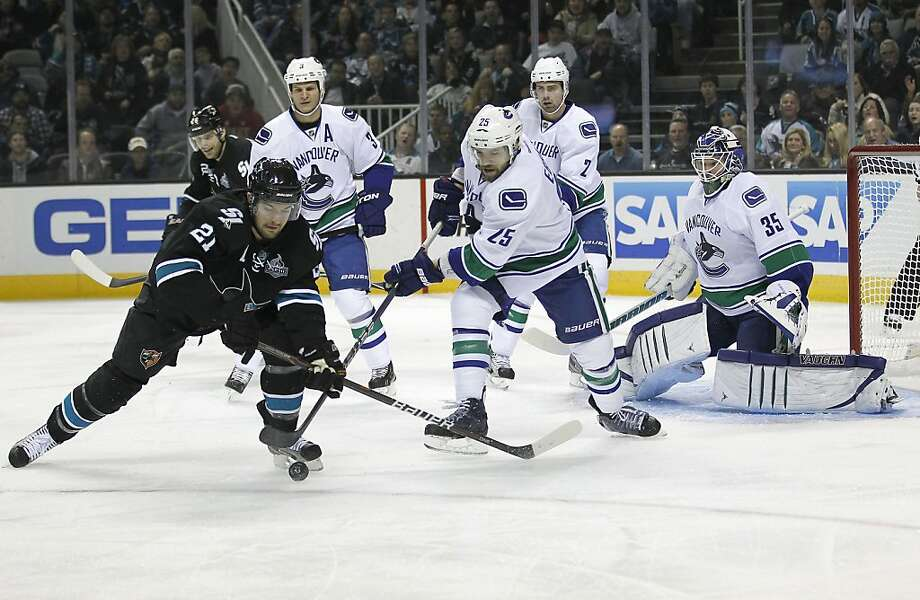 San Jose Sharks left wing T.J. Galiardi (21) battles for the puck in front of the goal against Vancouver Canucks center Andrew Ebbett (25) as Canucks goalie Cory Schneider (35) watches during the first period of an NHL hockey game in San Jose, Calif., Sunday, Jan. 27, 2013. (AP Photo/Tony Avelar) Photo: Tony Avelar, Associated Press
