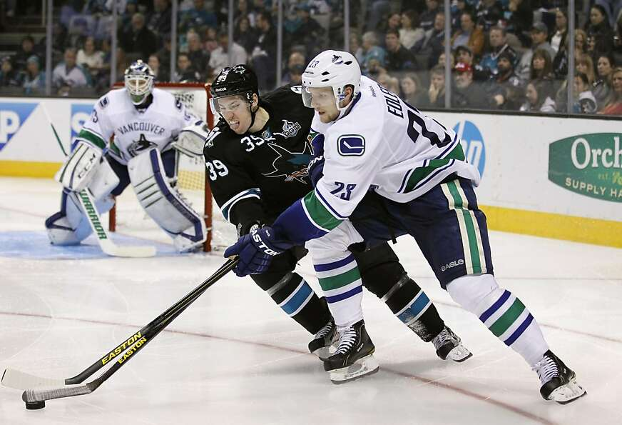 San Jose Sharks center Logan Couture (39) works against Vancouver Canucks defenseman Alexander Edler