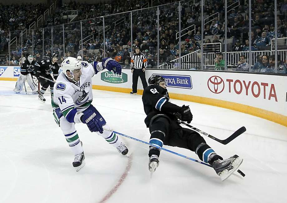 San Jose Sharks defenseman Justin Braun (61) is tripped by Vancouver Canucks center Alex Burrows (14) during the second period of an NHL hockey game in San Jose, Calif., Sunday, Jan. 27, 2013. (AP Photo/Tony Avelar) Photo: Tony Avelar, Associated Press