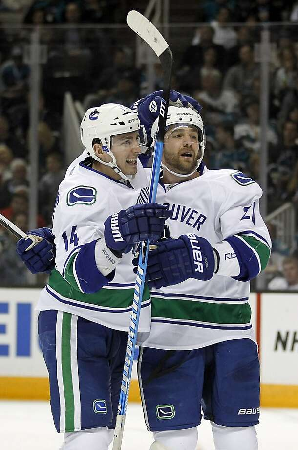 Vancouver Canucks center Alex Burrows (14) celebrates with left wing Chris Higgins (20) after scoring a goal against the San Jose Sharks during the second period of an NHL hockey game in San Jose, Calif., Sunday, Jan. 27, 2013. (AP Photo/Tony Avelar) Photo: Tony Avelar, Associated Press