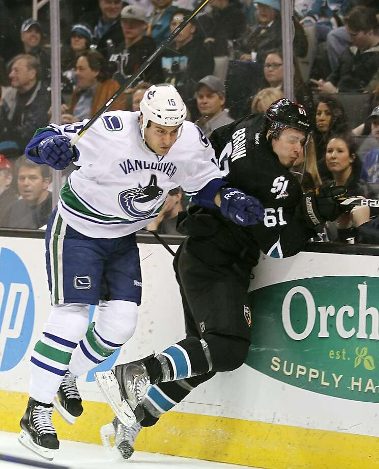 San Jose Sharks defenseman Justin Braun (61) is checked into the boards by Vancouver Canucks left wing Aaron Volpatti (15) during the second period of an NHL hockey game in San Jose, Calif., Sunday, Jan. 27, 2013. (AP Photo/Tony Avelar) Photo: Tony Avelar, Associated Press