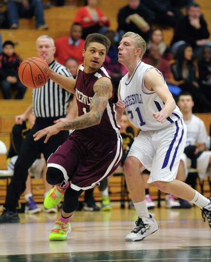 Jordan Gleason, left, of Watervliet drives towards the basket past Slater Nolan of Voorheesville dur