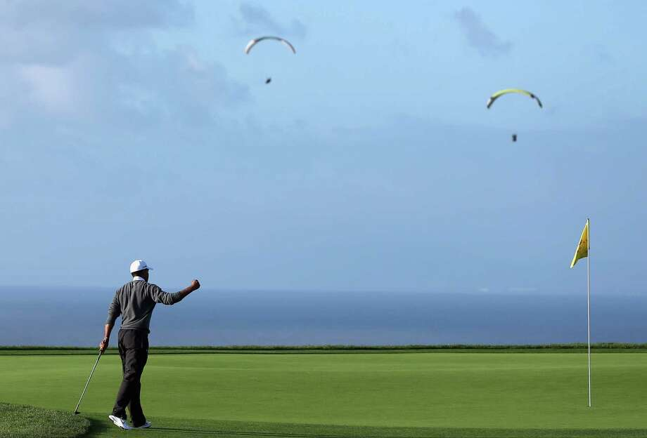 A couple of paragliders make like birdies in the sky as Tiger Woods sinks a birdie on the ground by chipping in on the fourth hole during the final round Sunday. Photo: Jeff Gross, Staff / 2013 Getty Images