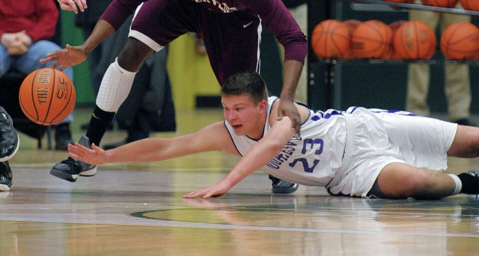 Logan Hotaling of Voorheesville dives to get the ball away from a  Watervliet player during their ga