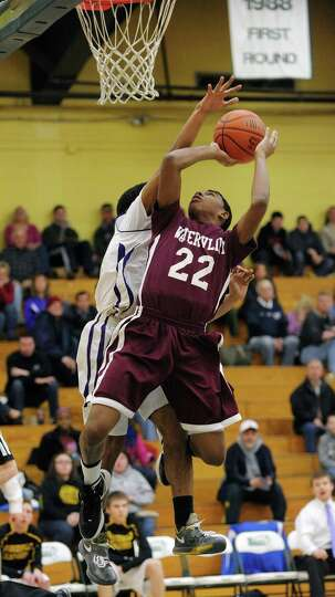 Henassy McConico, foreground, of Watervliet, puts up a shot as Noah Crawford of Voorheesville tries