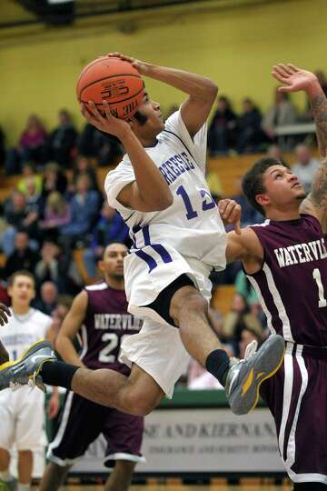 Noah Crawford of Voorheesville puts up a shot over Watervliet defenders as he drives towards the bas