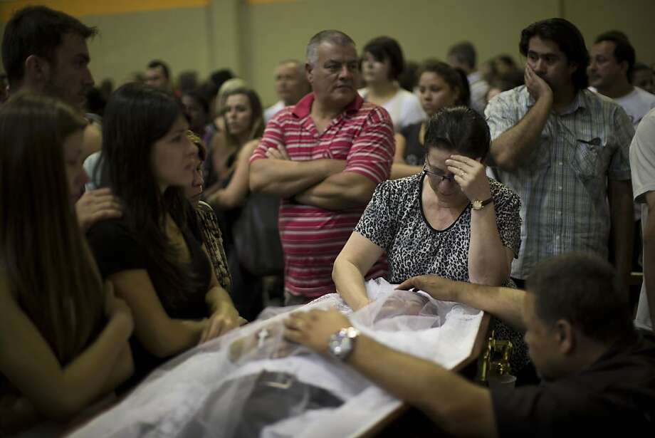 Relatives and friends mourn on the coffin containing the remains of a fire victim at a gymnasium where bodies were brought for identification in Santa Maria city, Rio Grande do Sul state, Brazil, Sunday, Jan. 27, 2013.  A fast-moving fire roared through the crowded, windowless Kiss nightclub in southern Brazil early Sunday, within seconds filling the space with flames and a thick, toxic smoke that killed more than 230 panicked partygoers who gasped for breath and fought in a stampede to escape.(AP Photo/Felipe Dana) Photo: Felipe Dana, Associated Press