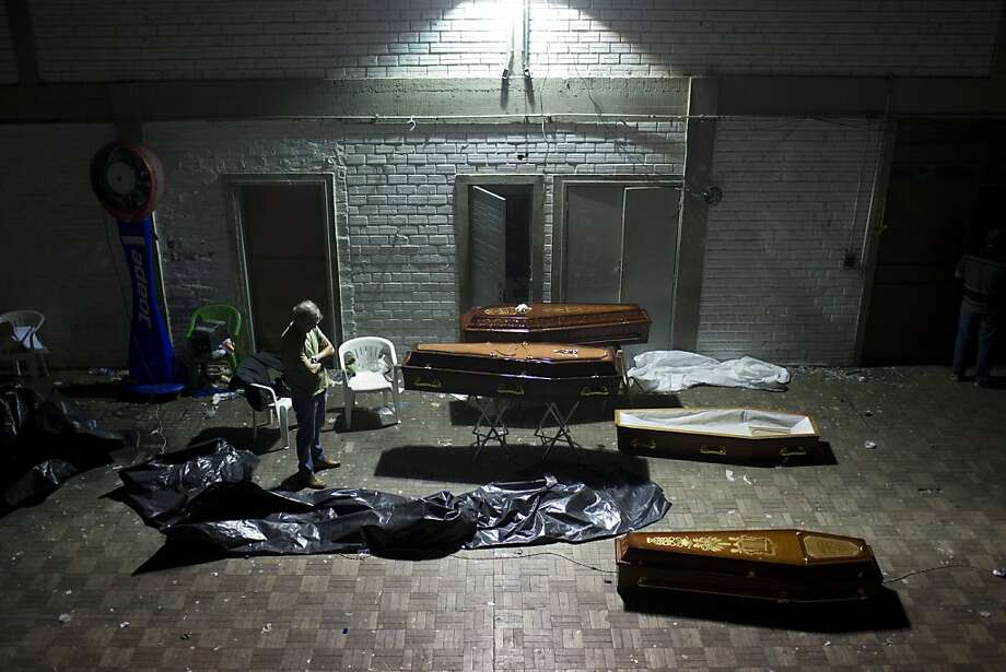 A man stands around coffins containing the remains of victims after the bodies were identified at a gymnasium in Santa Maria city, Rio Grande do Sul state, Brazil, Sunday, Jan. 27, 2013. A fast-moving fire roared through the crowded, windowless Kiss nightclub in southern Brazil early Sunday, within seconds filling the space with flames and a thick, toxic smoke that killed more than 230 panicked partygoers who gasped for breath and fought in a stampede to escape.(AP Photo/Felipe Dana) Photo: Felipe Dana, Associated Press