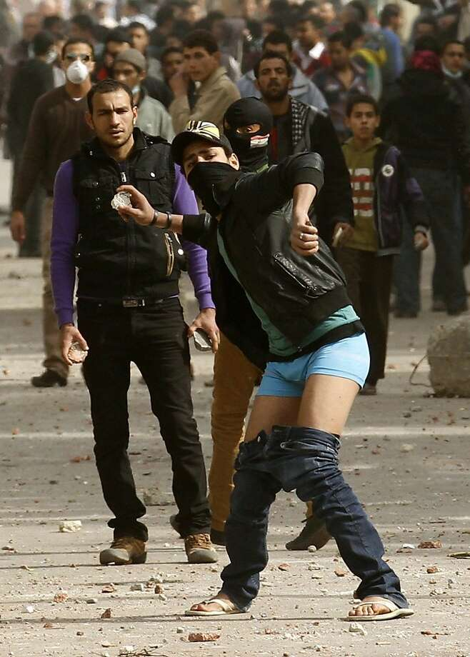 Let he who is without belt cast the first stone:An Egyptian protester's trousers slide down as he hurls a rock at riot police during a clash near Cairo's Tahrir Square. Photo: Mohammed Abed, AFP/Getty Images