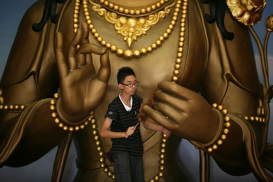 An Indonesian Chinese man cleans the Buddha statue in the preparation for the Lunar New Year celebrations in Satya Buddha Temple in Medan, North Sumatra, Indonesia, Sunday, Jan. 27, 2013. Photo: Binsar Bakkara, Associated Press