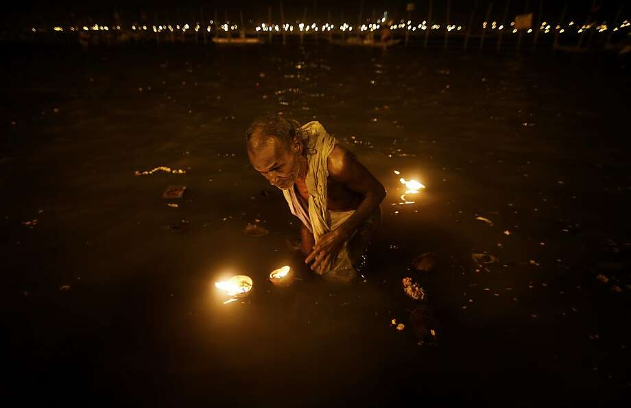 "A Hindu devotee takes a holy dip at ""Sangam,"" the meeting point of Indian holy rivers of Ganges, Yamuna and the mythical Saraswati, on occasion of ""Paush Purnima,"" considered to be very auspicious according to Hindu calendars, during the Maha Kumbh festival in Allahabad, India, Sunday, Jan. 27, 2013. Hundreds of thousands of Hindu pilgrims are expected to take a ritual dip at Sangam on Sunday. Millions of Hindu pilgrims are likely to attend the Maha Kumbh festival, which is one of the world's largest religious gatherings that lasts 55 days and falls every 12 years. Photo: Saurabh Das, Associated Press"