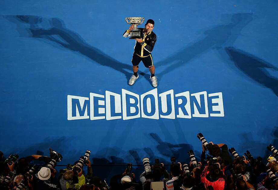 Serbia's Novak Djokovic poses with the winner's trophy after his victory over Britain's Andy Murray during the men's singles final on day 14 of the Australian Open tennis tournament in Melbourne on January 27, 2013. Photo: William West, AFP/Getty Images