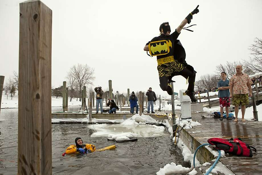 Brett Heppler, of Grand Haven, Mich., strikes a superhero pose as he jumps into the water during the second annual Polar Plunge, a fundraiser for the Tri-Cities Habitat for Humanity, at Chinook Pier in Grand Haven on Sunday, Jan. 27, 2013.  The plunge was the last event of Winter Fest. Heppler was the runner up in the costume contest this year. Photo: Ariana Van Den Akker, Associated Press