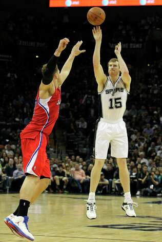 The Spurs' Matt Bonner (15) hits a big 3-pointer against Los Angeles Clippers' Blake Griffin (32) in the second half of their game at the AT&T Center on Monday, Nov. 19, 2012. Clippers defeated the Spurs, 92-87. Photo: Kin Man Hui, San Antonio Express-News / © 2012 San Antonio Express-News