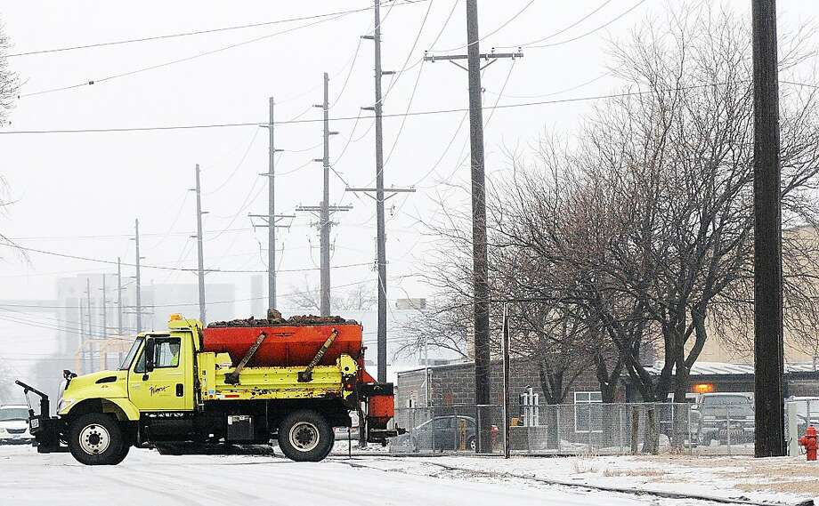 A city of Winona truck crosses Front Street while treating icy roads Sunday, Jan. 27, 2013, in Winona, Minn. A wintry mix of freezing rain, sleet and snow made for dangerous road conditions Sunday. Photo: Joe Ahlquist, Associated Press