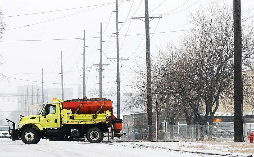 A city of Winona truck crosses Front Street while treating icy roads Sunday, Jan. 27, 2013, in Winon