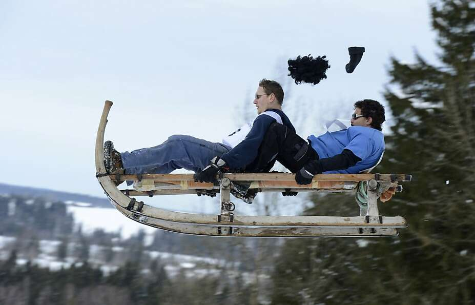 Participants jump with their sled during the traditional Schnablerrennen sledge race in a valley nea