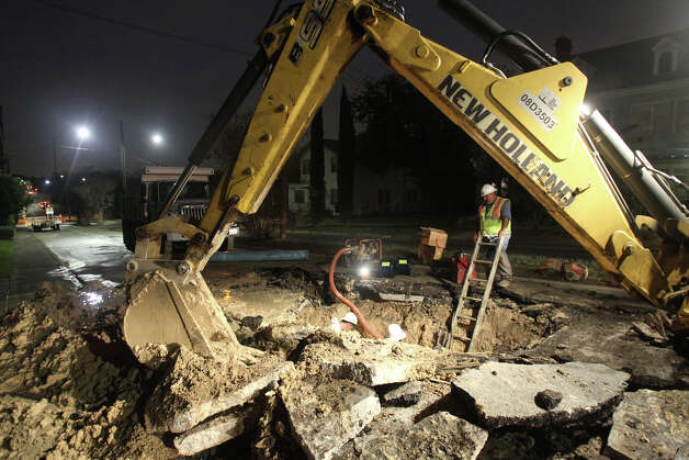 A San Antonio Water System crew works to repair a water main break in the eastbound lane of Woodlawn Avenue near North Flores Street after the pipe ruptured around 4 a.m. Monday. Photo: John Davenport, San Antonio Express-News / ©San Antonio Express-News/Photo Can Be Sold to the Public