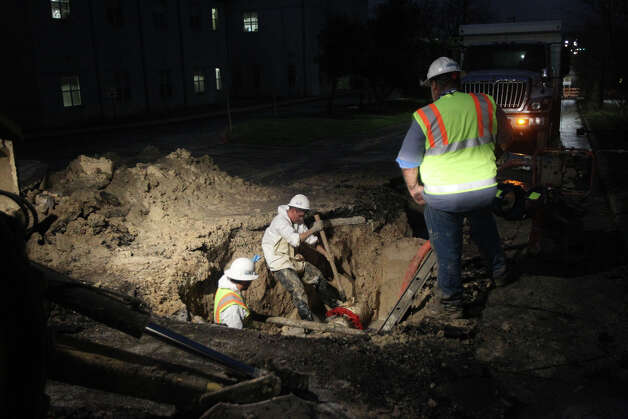 A San Antonio Water System crew works to repair a water main break Monday January 28, 2013  on the eastbound lane of Woodlawn near North Flores street after the pipe ruptured early Monday morning. The eastbound lane of Woodlawn near Flores will remain closed until the repairs are completed. Photo: JOHN DAVENPORT, San Antonio Express-News / © San Antonio Express-News